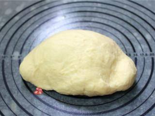 牛奶面包,将和好的面团取出,在案板上揉出面团内的气泡,手揉约10分钟左右,再搓成长条。