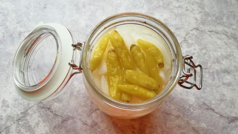 泡椒萝卜条,将调好的泡椒糖醋水倒入密封罐,没过萝卜条,放入泡椒,盖上密封罐的盖子。