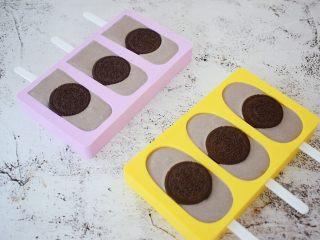 奥利奥雪糕,然后再表面各放一块奥利奥饼干,用手按压一下,使其服贴,然后放入冰箱冷冻一夜,第二天就可以取出食用了