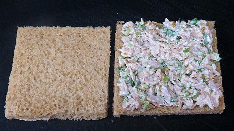 全麦红糖吐司(一键式)+金枪鱼芹菜三明治,取一片吐司片,把金枪鱼拌酱涂抹均匀