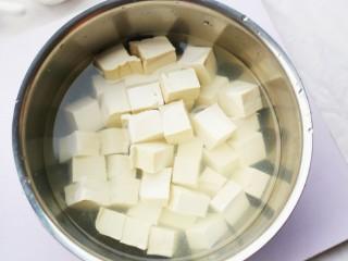 鲜掉眉毛的丝瓜豆腐汤,豆腐切成小块,然后加入淡盐水中浸泡15分钟。(这样一来可以去除豆腥味,二来在炒的时候,可以让豆腐的形状更加完整。)