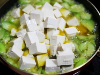 鲜掉眉毛的丝瓜豆腐汤,把沥干水的豆腐捞出放入锅中。