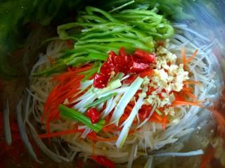香辣凉拌三丝,把土豆丝胡萝卜丝控干水份放入盆中 加入尖椒丝,加入葱蒜干红辣椒