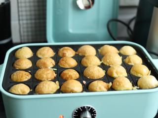 章鱼小丸子,待定型以后借助竹签翻面,把另一面也烤的金黄。