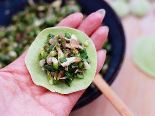 槐花韭菜翠玉饺子,擀好的面皮上,放入适量调制好的馅料。
