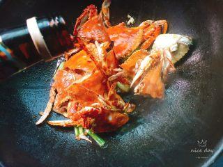姜葱炒螃蟹,接着放入适量料酒炒匀