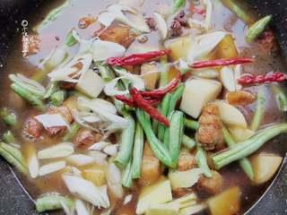 五花肉豆角焖面,加适量开水至与菜平齐的程度。放入干辣椒、八角、葱姜蒜、盐、一小勺老抽熬煮