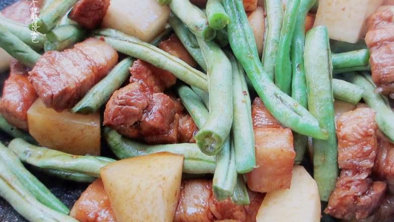 五花肉豆角焖面,倒入土豆跟豆角大火翻炒,翻炒至豆角变色,翻炒一分钟左右就可以