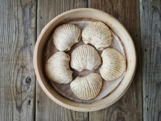 贝壳饼夹,将贝壳饼夹生坯入笼再次醒发10-15分钟,上锅隔水大火蒸15分钟,关火后焖3分钟,出笼。