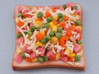 田园时蔬吐司披萨,我在芝士碎上又撒了一些时蔬碎,这样就可以让宝贝多吃一些蔬菜咯。