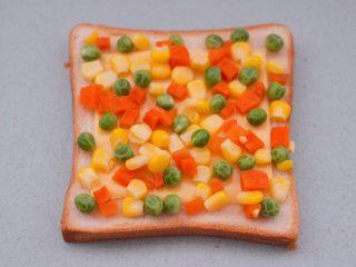 田园时蔬吐司披萨,把焯过水的玉米粒和豌豆,胡萝卜丁均匀地铺上奶酪片上。