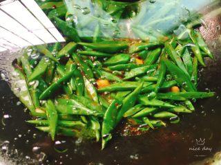 酱爆刀豆,加入适量清水,翻炒一下盖上锅盖焖两三分钟,豆类一定要熟透才能吃