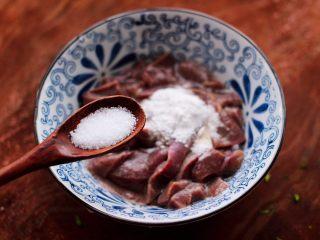 生滚猪肝时蔬小米粥,把浸泡过的猪肝重新洗净后,放入淀粉和适量的盐调味。
