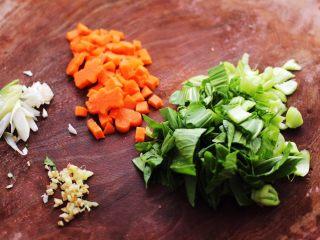 生滚猪肝时蔬小米粥,小油菜摘洗干净后,用刀切碎,葱姜切碎,胡萝卜切小丁备用。