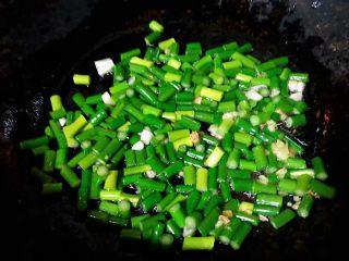 蒜苔辣炒鸡胗,锅中倒入适量油加热放入姜爆香再放入蒜苔大火翻炒