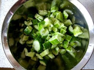 花生米拌黄瓜,把切好的黄瓜放入盆中