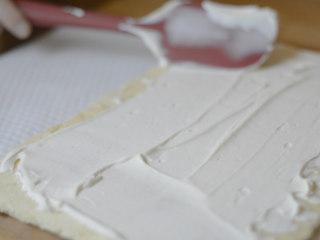 草莓牛乳奶冻卷,淡奶油打发到固态。 均匀涂抹一半奶油到蛋糕片上。