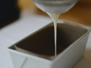 草莓牛乳奶冻卷,在模具中垫油纸,把奶冻过滤到模具中。