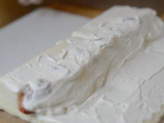 草莓牛乳奶冻卷,如果草莓比较大,需要切掉一点奶冻。淡奶油用量需根据实际情况自行增减。盖上剩余的奶油。