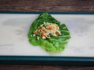 春日包菜饭便当,铺上一张焯过水的包菜,在包菜上放上适量的鸡肉什锦炒饭。