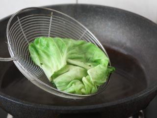 春日包菜饭便当,将一片片的包菜焯水,焯水后过凉水,沥干水分备用。