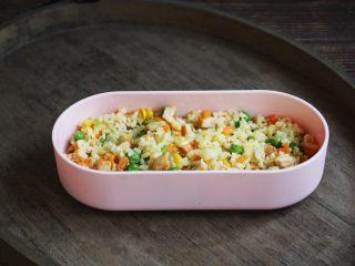 春日包菜饭便当,将一部分鸡肉什锦炒米饭铺在便当盒的底部。