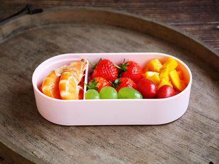 春日包菜饭便当,将鲜虾放在便当盒的小隔断盒里,依次放入草莓、葡萄、芒果、小番茄。