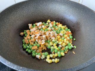 春日包菜饭便当,放入胡萝卜、豌豆、玉米、鸡肉丁,翻炒1分钟。