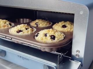 金酥粒蓝莓爆浆蛋糕,放入已经提前预热到185度的东菱3706日系小烤箱里,烘烤25分钟左右(实际烘烤温度要根据自家烤箱脾气而定)
