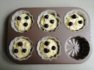 金酥粒蓝莓爆浆蛋糕,挤入一半的蛋糕糊,放上三粒草莓