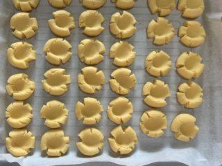 玛格丽特饼干,取出后分成10g左右等分小剂子,搓圆用拇指按压成如图形状,同时烤箱预热170度