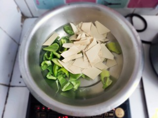 家常尖椒炒豆片,水开后将食材放入,焯水。