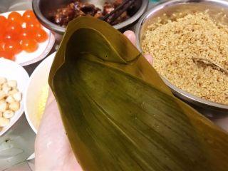 瑶柱咸蛋黄鲜肉粽,取两片粽叶折成漏斗状