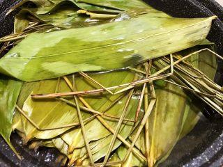 瑶柱咸蛋黄鲜肉粽,干粽叶清水浸泡2个小时后,放入锅中加水煮15分钟,捞出后用清水一片一片清洗干净备用