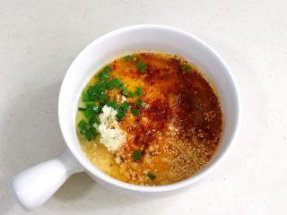 酸辣凉拌面,提前把白芝麻、蒜末、葱花和辣椒面放入碗内,把适量的食用油加热淋入其中。