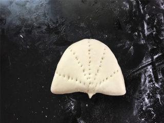玉米粉荷叶饼,然后把面片对折折起来,用叉子叉上花纹,也可以用干净的梳子在上面压出花纹。