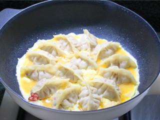 鸡蛋煎饺,端起煎锅左右摇晃一下,让蛋液均匀铺在饺子周围,调成中火煎至蛋液凝固;