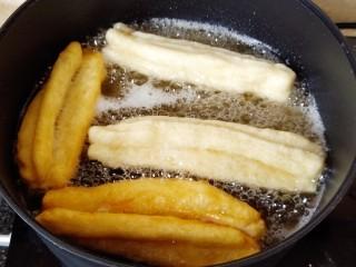 简单快手炸油条,先来炸大油条,把锅里油烧热,放入油条炸制,