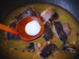 酱焖安康鱼,锅中加入盐和白砂糖。