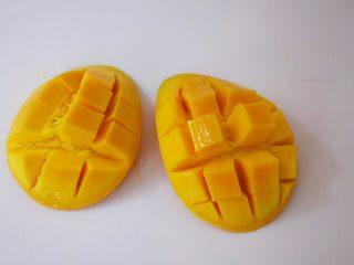 芒果西米露,芒果芒果核为中心,在果核右边切一刀,芒果被分为两部分,取芒果果肉上划格子,但是注意不要切到皮,把划好格子的芒果拿在手上,手指抵住芒果皮往上顶,再用刀切出果肉即可