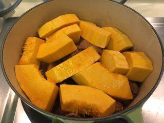 南瓜煮小排,时间到加入南瓜,稍微拌一下让南瓜沾上酱汁