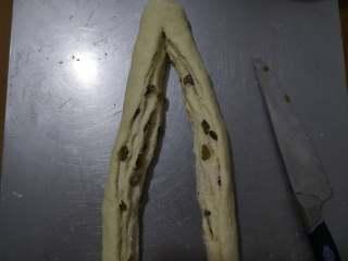 好吃又好看的椰蓉葡萄干吐司,卷好后,用刀将面团分割开,顶部最好不要切断。