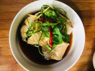 清蒸银鳕鱼,把蒸好的鱼放入碗中,浇上调好的汁,在鱼段上放上葱姜小米椒丝和香菜段点缀一下