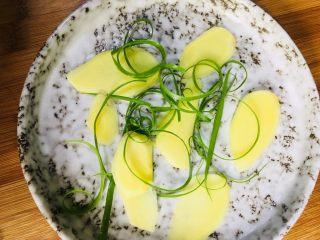清蒸银鳕鱼,取一个干净的盘子,底部铺上一层姜片和葱丝