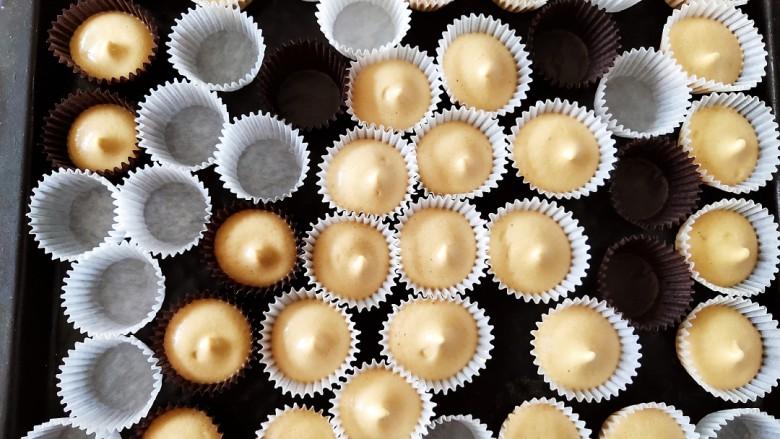 咖啡小蛋糕,这时候烤箱可以提前预热,然后把小纸杯摆在烤盘中,把蛋糕糊装在裱花袋内,一个个挤入蛋糕糊即可。
