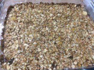 减肥香蕉燕麦棒,取出一个方形模具,底下铺保鲜膜,将混合好的材料倒入,压平整;