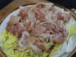 娃娃菜蒸鸡腿,将娃娃菜摆在一个干净的盘子里,然后把腌制好的鸡腿肉均匀地铺在娃娃菜上,把腌制鸡肉的料汁也倒进来。