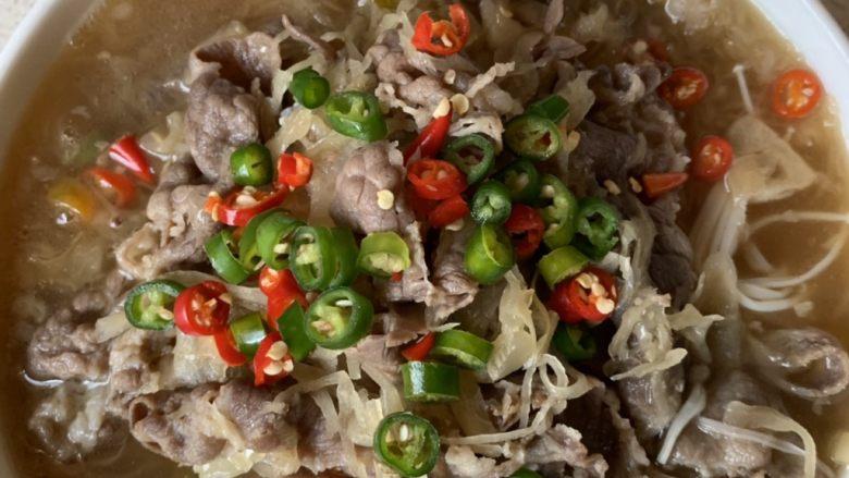 酸汤肥牛,碗中放上青红尖椒圈,烧一点热油,浇在辣椒上。滋啦滋啦……这道热气腾腾的酸汤肥牛就做好啦!鲜美无比,爆好吃!
