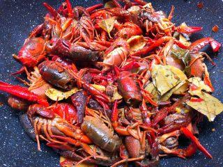 麻辣小龙虾,倒入小龙虾翻炒一会,炒至小龙虾微微的变色,加入适量盐和适量白糖翻炒均匀。