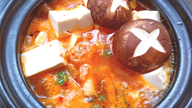 辣白菜鱼片豆腐煲,放上香菇,盖上盖子焖10分钟